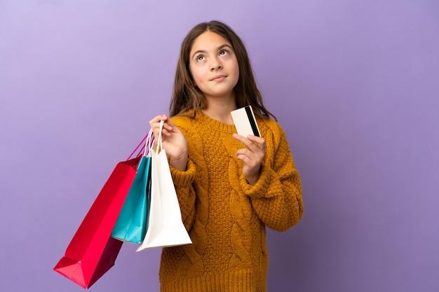 Kleines kaukasisches mädchen isoliert auf lila hintergrund, das einkaufstüten und eine kreditkarte hält und denkt