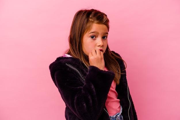 Kleines kaukasisches mädchen isoliert auf rosa beißenden fingernägeln, nervös und sehr ängstlich.