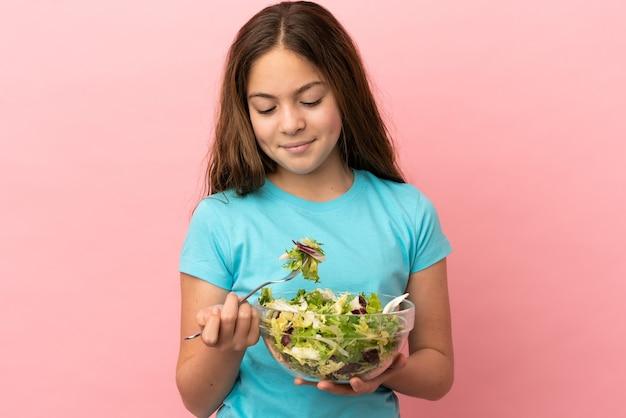 Kleines kaukasisches mädchen isoliert auf rosa hintergrund, das eine schüssel salat mit glücklichem ausdruck hält