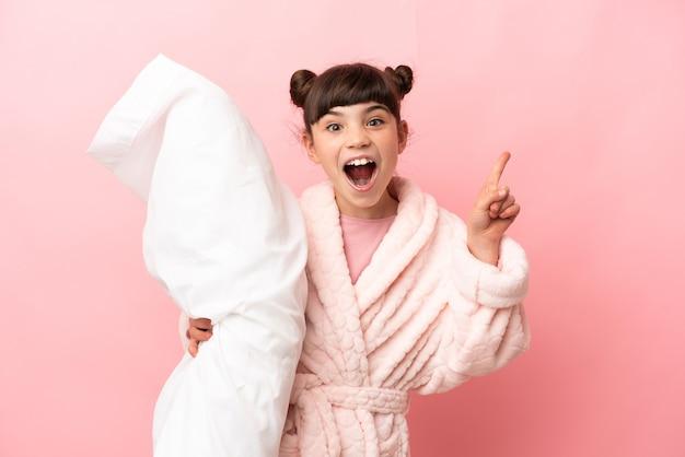 Kleines kaukasisches mädchen isoliert auf rosa hintergrund im pyjama und zeigt eine großartige idee