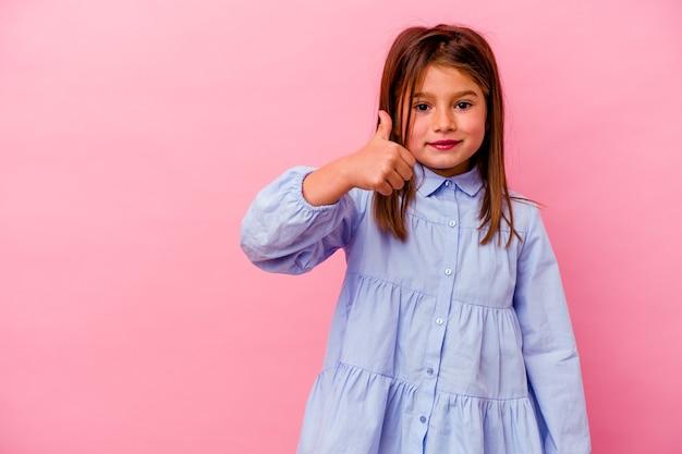 Kleines kaukasisches mädchen isoliert auf rosa hintergrund lächelt und hebt den daumen hoch