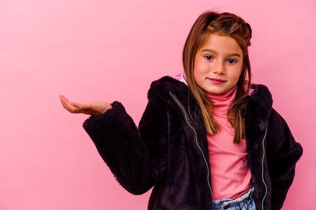 Kleines kaukasisches mädchen isoliert auf rosafarbenem hintergrund, das einen kopienraum auf einer handfläche zeigt und eine andere hand an der taille hält.