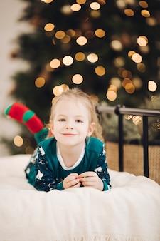 Kleines kaukasisches mädchen liegt auf dem bett nahe dem weihnachtsbaum und lächelt