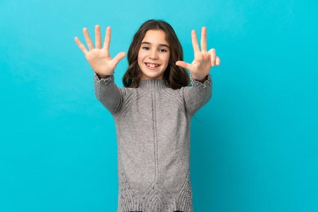 Kleines kaukasisches mädchen lokalisiert auf blauer wand, die acht mit den fingern zählt