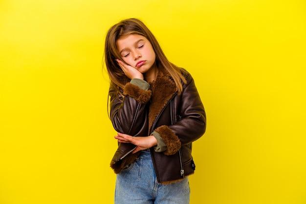 Kleines kaukasisches mädchen lokalisiert auf gelb, das gelangweilt, müde ist und einen entspannten tag braucht.