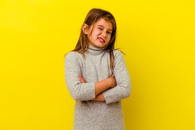 Kleines kaukasisches mädchen lokalisiert auf gelbem unglücklichem schauen in der kamera mit sarkastischem ausdruck.
