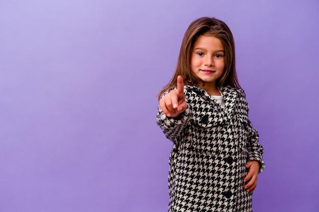 Kleines kaukasisches mädchen lokalisiert auf lila wand, die nummer eins mit finger zeigt.