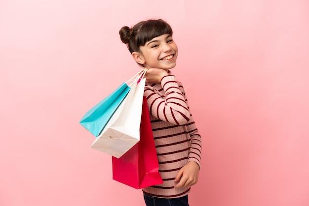 Kleines kaukasisches mädchen lokalisiert auf rosa wand, die einkaufstaschen hält und lächelt