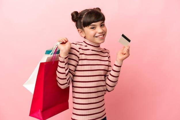 Kleines kaukasisches mädchen lokalisiert auf rosa wand, die einkaufstaschen und eine kreditkarte hält