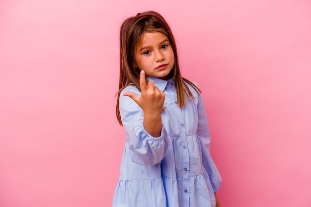 Kleines kaukasisches mädchen lokalisiert auf rosa wand, die mit dem finger auf sie zeigt, als ob die einladung näher kommt.