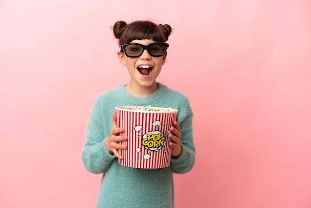 Kleines kaukasisches mädchen lokalisiert mit 3d-brille und hält einen großen eimer popcorn