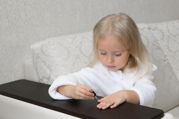Kleines kaukasisches mädchen malt nägel auf händen.