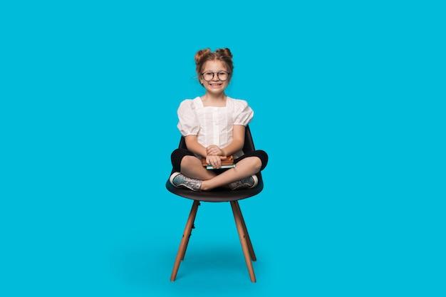 Kleines kaukasisches mädchen mit brille lächelt an der kamera, während auf dem stuhl sitzend ein buch auf einer blauen studiowand sitzt