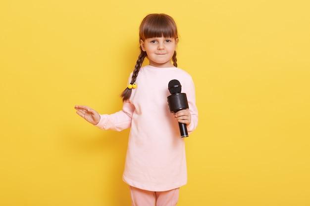 Kleines kaukasisches mädchen tanzt und singt mit mikrofon in den händen, niedliches kleines kind gab vor, superstar zu sein, konzert gegen gelbe wand arrangierend, handfläche beiseite spreizend.