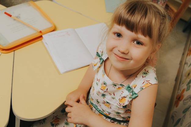 Kleines kaukasisches schulmädchen, das gerade in die kamera schaut. lächelndes schulmädchen, das am tisch sitzt. zurück zum schulkonzept.