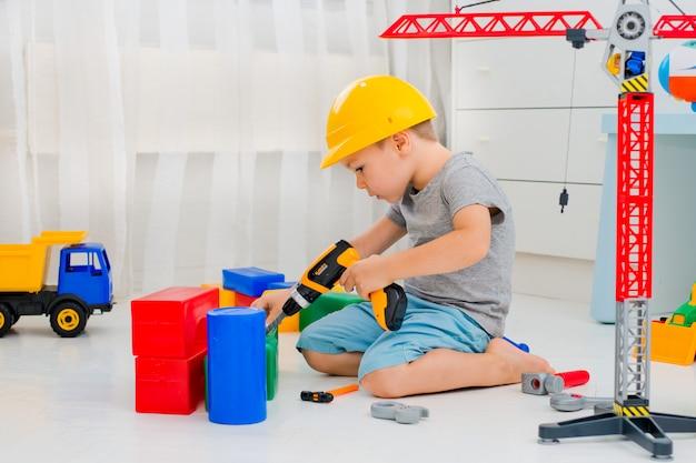 Kleines kind 4 jahre alt, spielt mit vielen bunten plastikspielzeugen im raum