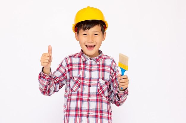 Kleines kind als bauarbeiter mit gelbem helm und pinsel in der hand