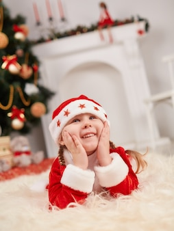 Kleines kind als weihnachtsmann mit den händen auf gesicht gekleidet