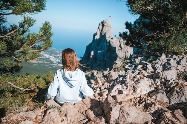 Kleines kind am rande der klippe in den bergen