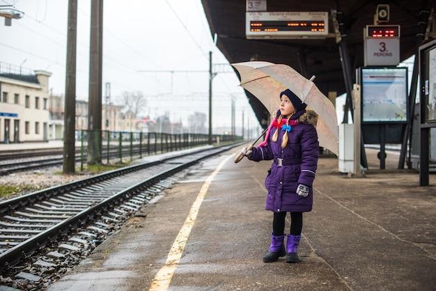 Kleines kind auf bahnsteig mit einem regenschirm auf einem bahnhof