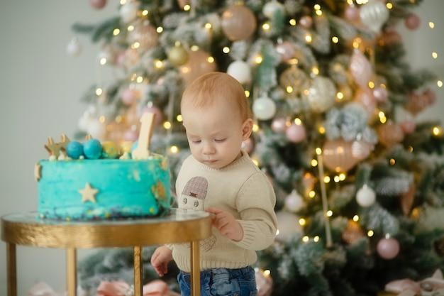 Kleines kind auf dem hintergrund des weihnachtsbaumes, kindergeburtstag