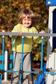 Kleines kind, das auf buntem spielplatz im herbst spielt