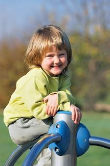 Kleines kind, das auf buntem spielplatz in einem park spielt