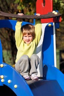 Kleines kind, das auf buntem spielplatz spielt