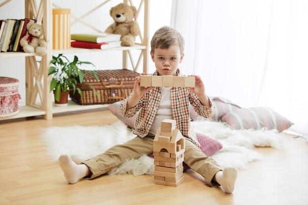 Kleines kind, das auf dem boden sitzt. hübscher junge, der zu hause mit holzwürfeln spielt. konzeptbild mit kopie oder negativraum und modell für ihren text