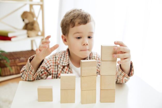 Kleines kind, das auf dem boden sitzt. hübscher junge, der zu hause mit holzwürfeln spielt. konzeptbild mit kopie oder negativraum