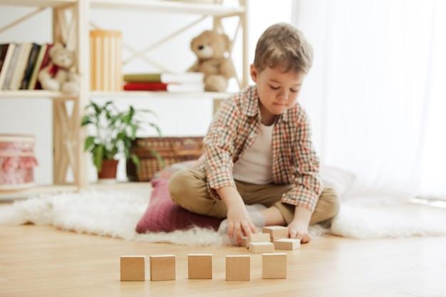 Kleines kind, das auf dem boden sitzt. hübscher junge, der zu hause mit holzwürfeln spielt.