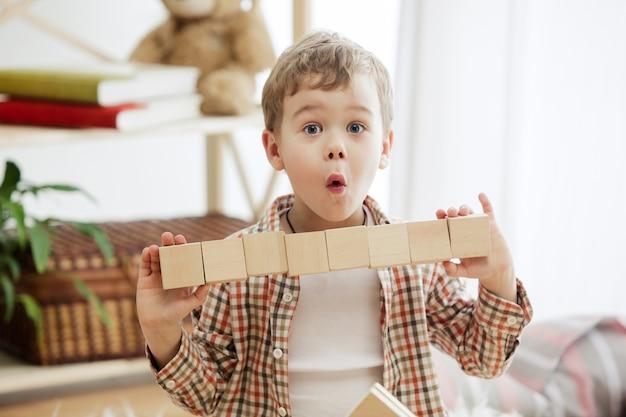 Kleines kind, das auf dem boden sitzt. hübscher lächelnder überraschter junge, der zu hause mit holzwürfeln spielt. konzeptbild mit kopie oder negativraum und modell für ihren text.