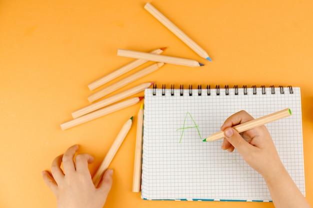 Kleines kind, das auf dem papier zeichnet