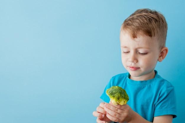 Kleines kind, das brokkoli in seinen händen auf blau hält