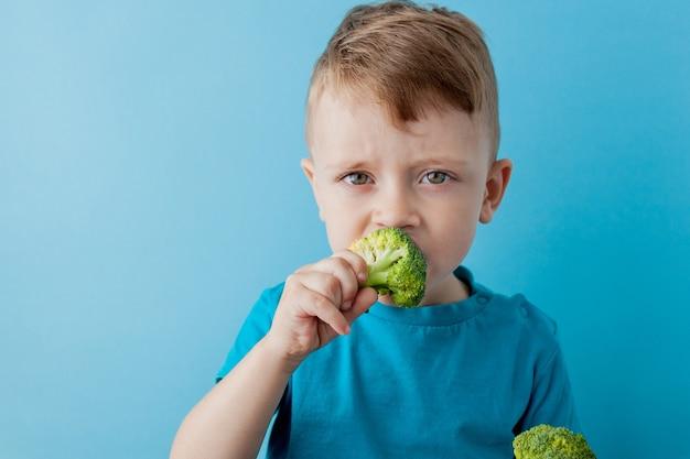 Kleines kind, das brokkoli in seinen händen hält. veganes und gesundes konzept.
