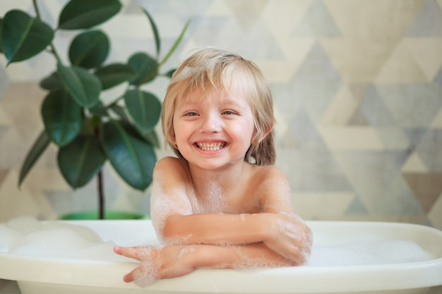 Kleines kind, das ein bad in einem schönen badezimmer mit blauer wand und blumen nimmt. kinderhygiene.