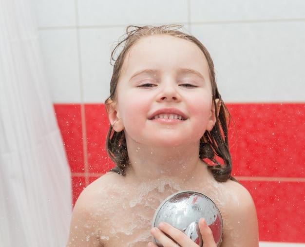 Kleines kind, das eine dusche genießt