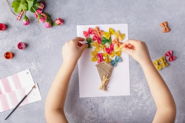 Kleines kind, das einen blumenstrauß aus farbigem papier und farbigen teigwaren heraus tut.