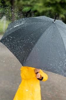 Kleines kind, das einen großen schwarzen regenschirm hält