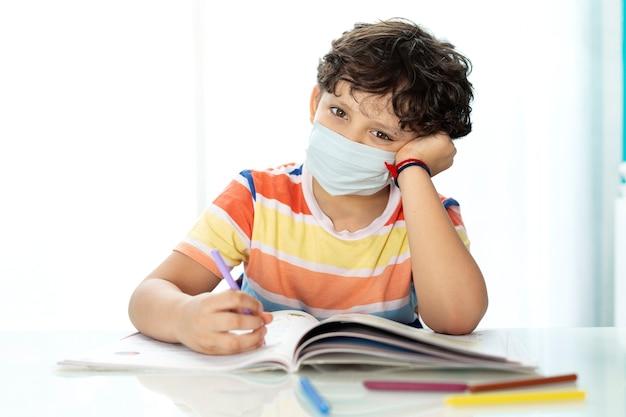 Kleines kind, das hausaufgaben zu hause macht. er trägt eine gesichtsmaske.