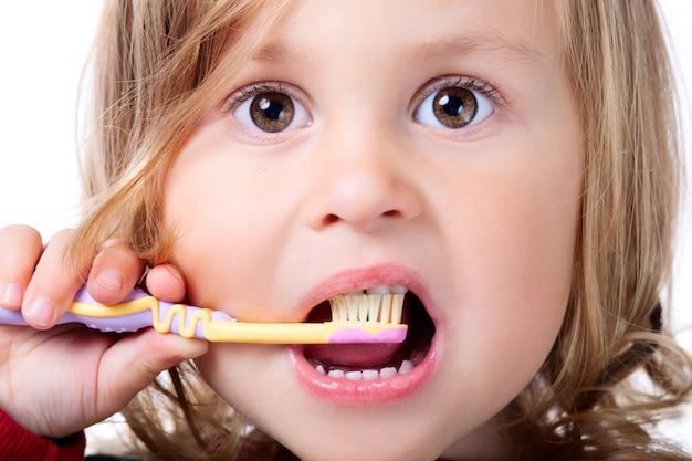 Kleines kind, das ihre zähne putzt
