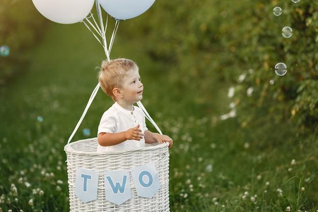 Kleines kind, das im korb mit luftballons sitzt