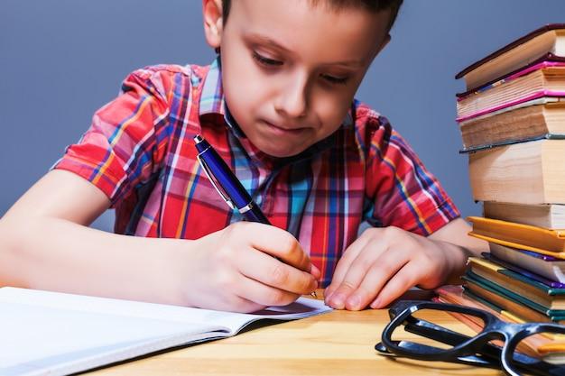 Kleines kind, das im notizbuch, schulhausaufgabenkonzept schreibt. junger schüler am schreibtisch im klassenzimmer