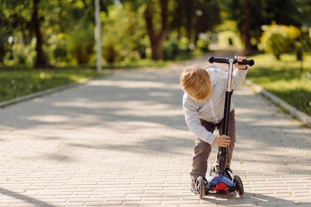 Kleines kind, das lernt, einen roller im freien zu fahren