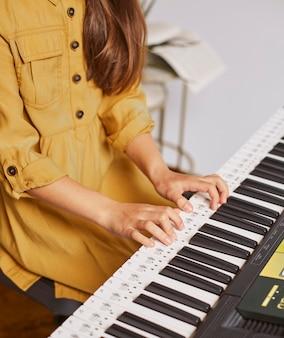 Kleines kind, das lernt, wie man die elektronische tastatur spielt