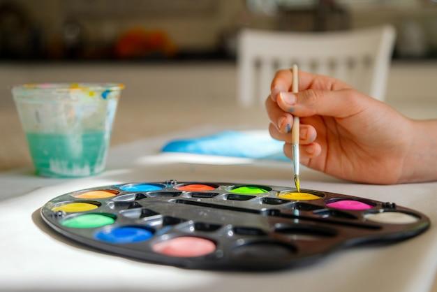 Kleines kind, das mit aquarellfarbe an der hauptschule malt.