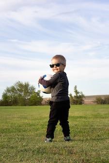 Kleines kind, das mit ball auf fußballplatz spielt