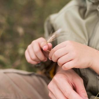 Kleines kind, das mit einer weizenpflanze spielt