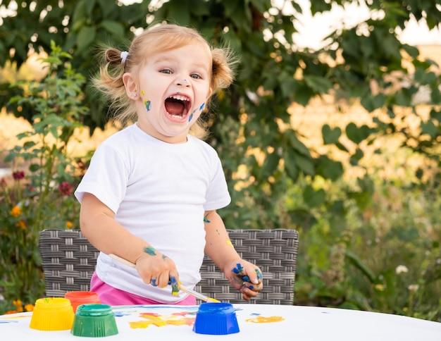 Kleines kind, das mit farbe und pinsel zeichnet. nettes kleines mädchen, das bild im garten malt, draußen zu hause im hinterhof