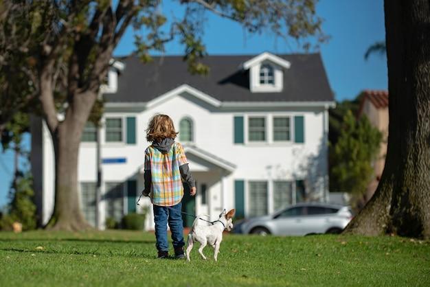 Kleines kind, das mit hund im garten spazieren geht, glückliche kindheit